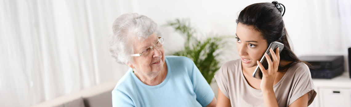 Young woman speaks on phone while elderly woman watches her