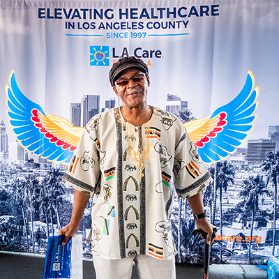 a man standing in front of L.A. Care's Elevating Health Care photo backdrop