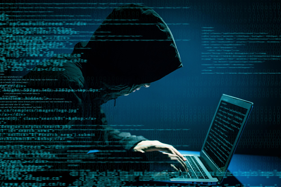 hooded figure hacking on laptop