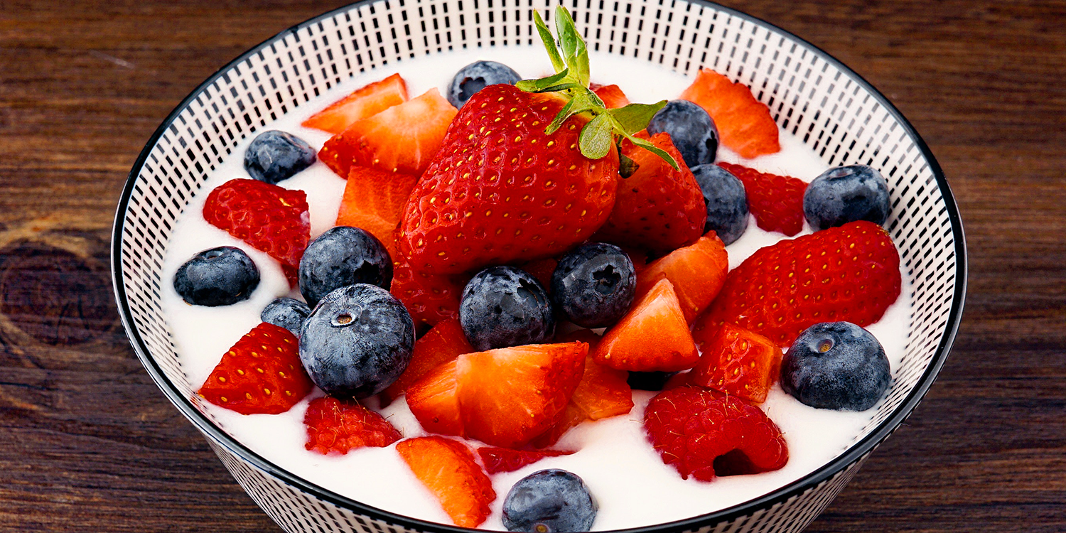 a bowl of fresh strawberries and blueberries on yogurt