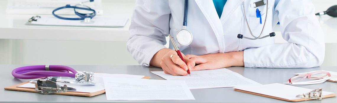 doctor filling out paperwork at her desk