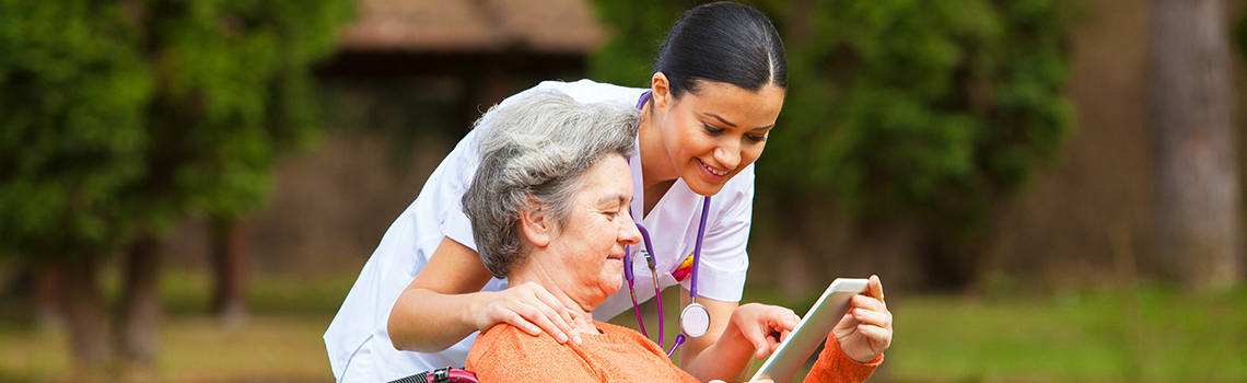 Nurse teaching woman in wheelchair how to use ipad