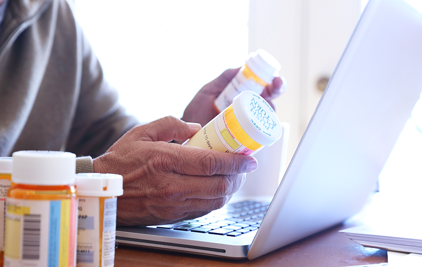 hands with pill bottles and laptop