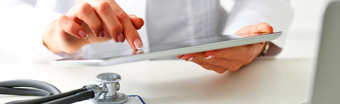 doctor's hands holding a tablet computer