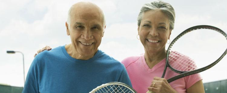 smiling older couple with tennis rackets